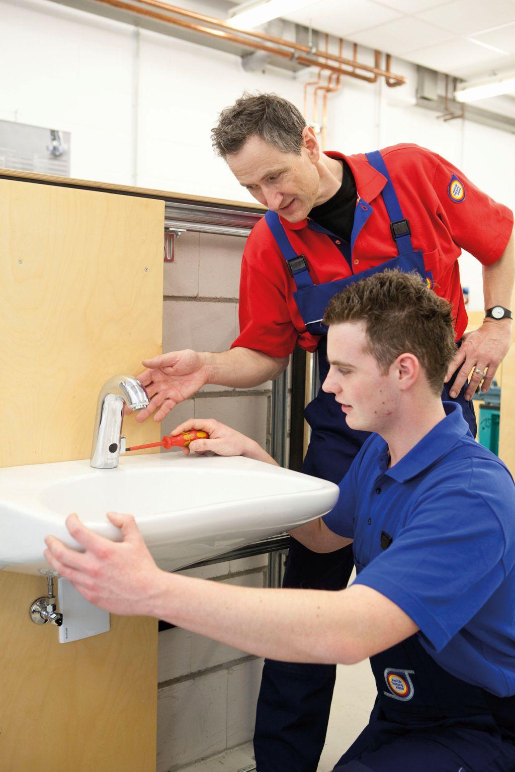 Zwei Anlagenmechaniker reparieren ein Waschbecken