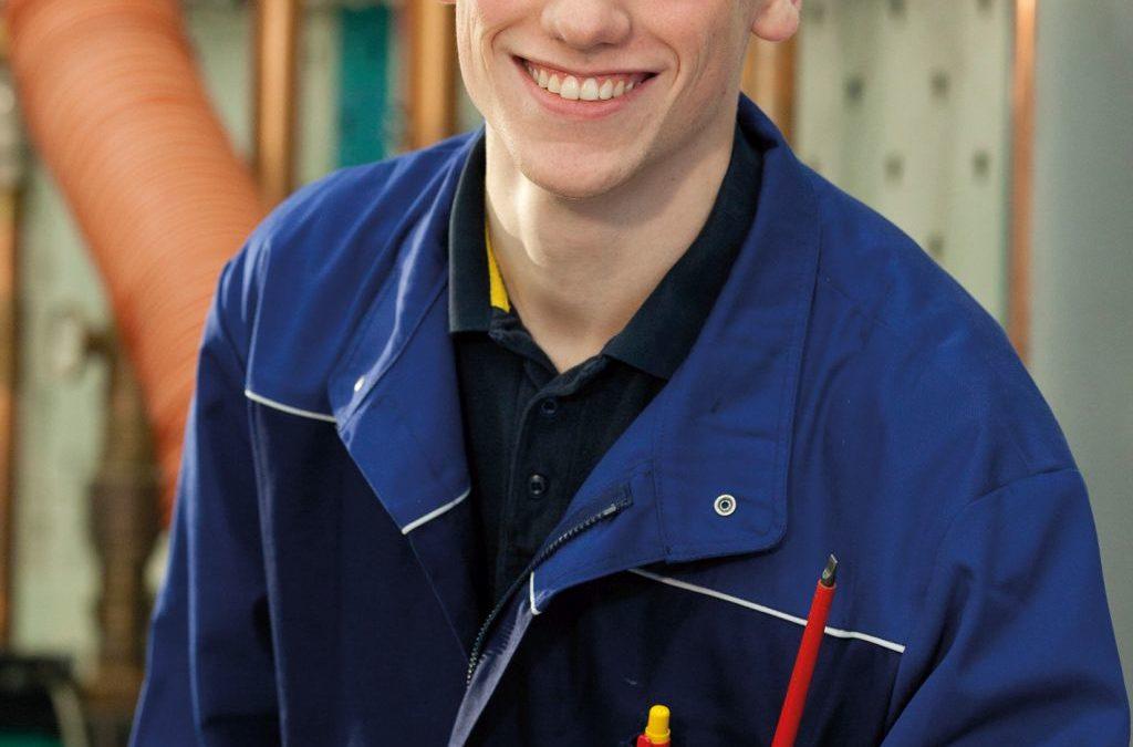 Junger Mann in blauer Handwerkerkleidung ist glücklich in seinem Beruf.