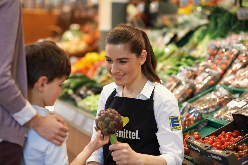 Junge Edekaverkäuferin berät einen Jungen in der Gemüseabteilung. (Chancengleichheit)