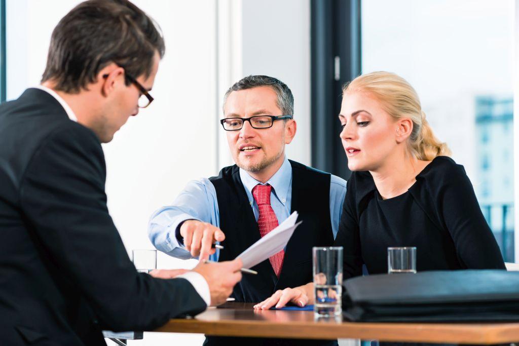 Junger Mann im Bewerbungsgespräch mit einem Mann und einer Frau.