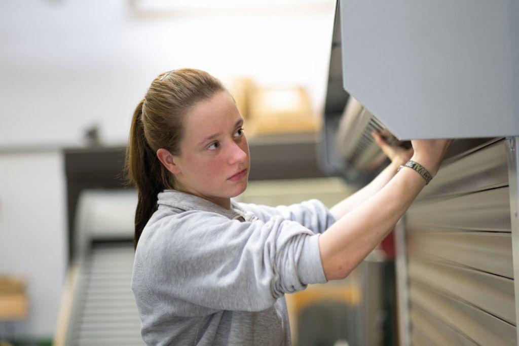 Junge Frau bei der Arbeit am Rollladenkasten. (RS-Mechatroniker)
