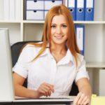 Büromanagement: Junge Frau am Schreibtisch. Dahinter Regal mit Aktenordnern.