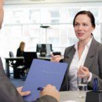 Frau im Gespräch. Im Vordergrund hält ein Mann eine Bewerbungsmappe (Arbeitsmarkt)