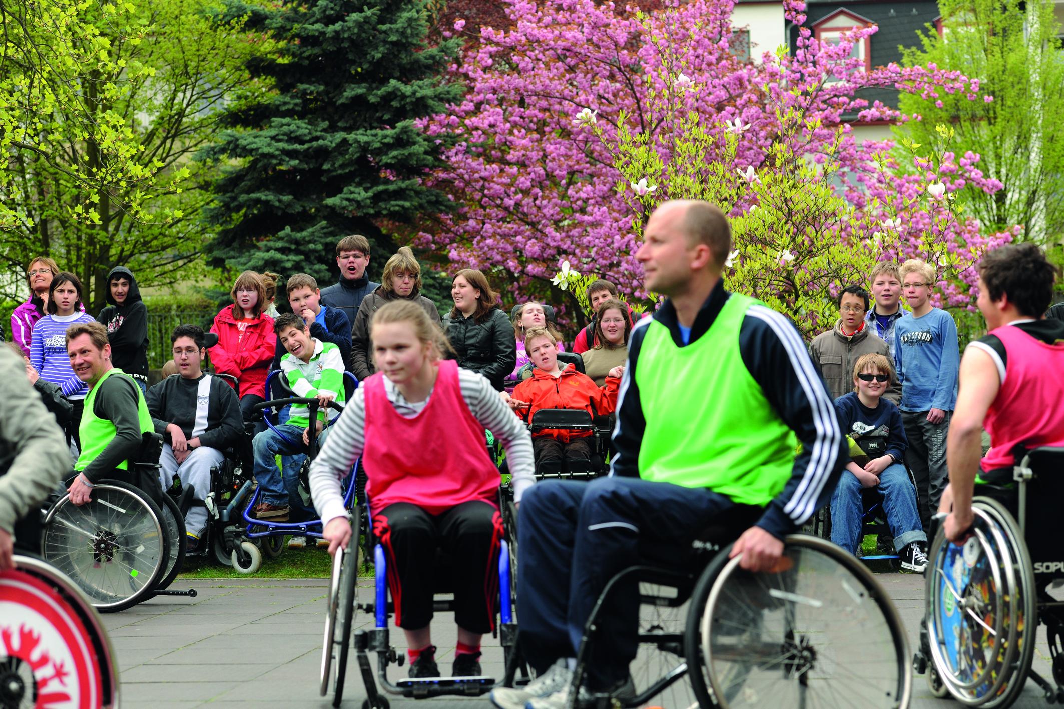 Jugendliche mit Behinderung schauen Rollstuhlfahrern beim Spiel zu.