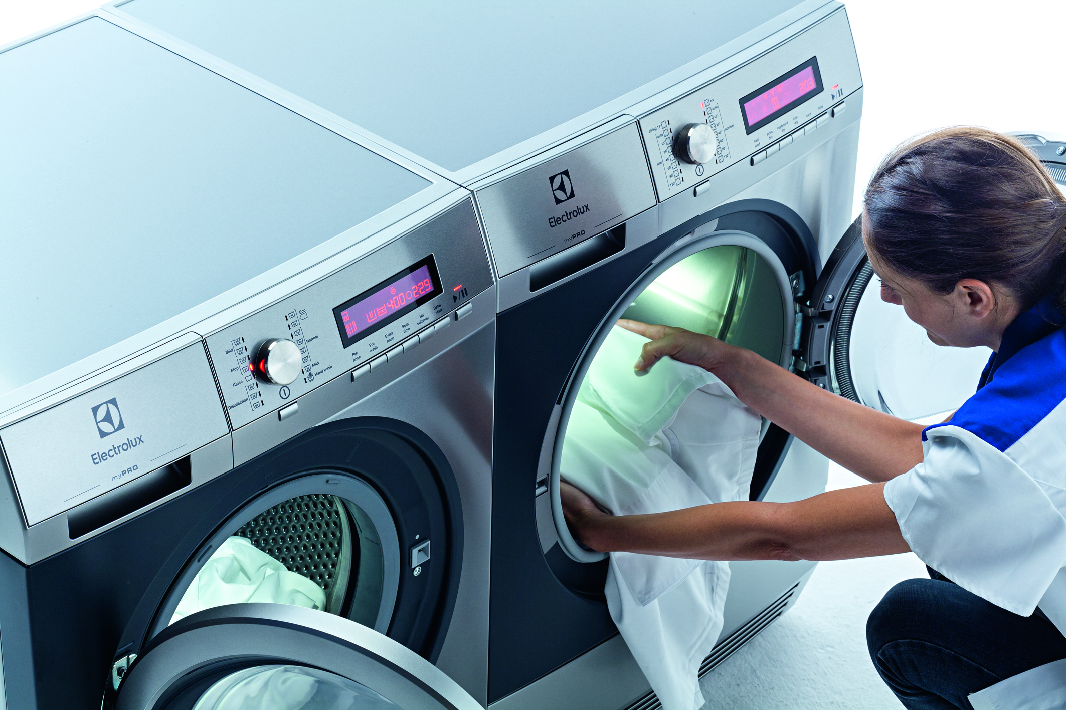 Eine Mitarbeiterin befüllt eine Profi-Waschmaschine