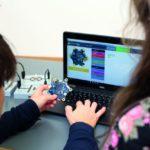 Schüler programmieren an einem Laptop.