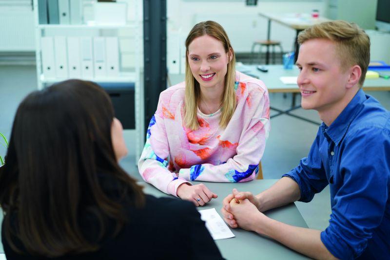 Zwei junge Auszubildende im Gespräch mit einer Kollegin. (Berufsstart)
