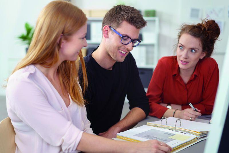 Gutes Verhältnis: drei Arbeitskollegen sitzen zusammen und besprechen sich
