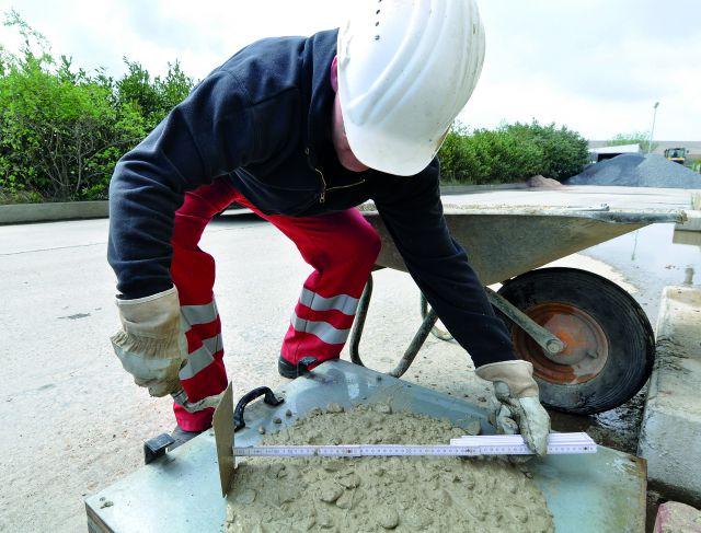 Ein Baustoffprüfer in Arbeitskleidung untersucht Arbeitsmaterial