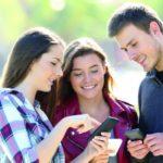 So gelingen die Abiturprüfungen: eine Gruppe von Jugendlichen schauen gemeinsam auf ein Smartphone und lernen somit für ihr Abitur