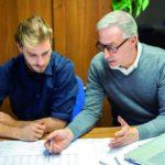 Zwei Männer, verschiedener Generationen, arbeiten zusammen im Büro