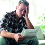 Bewerbung wurde abgelehnt! Ein Mann sitzt traurig auf dem Sofa und hält seine Absage in den Händen