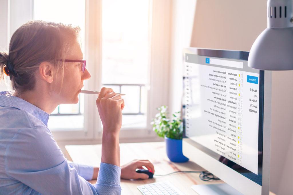 Die perfekte Bewerbung: Junge Frau sitzt vor einem Bildschirm und überlegt.