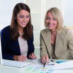 Der Frauenanteil in Führungspositionen soll wachsen: Zwei Frauen sitzen zusammen am Arbeitsplatz und besprechen ein Dokument