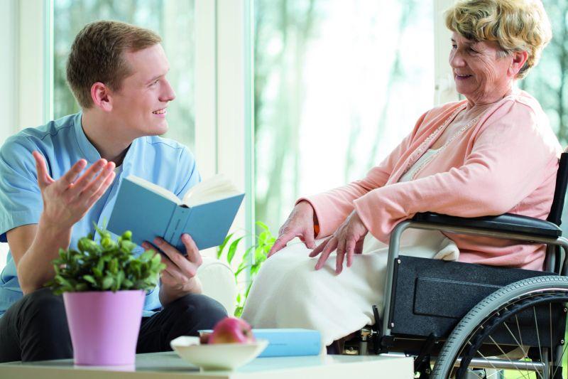 Eine männliche Pflegekraft ist glücklich und liest einer älteren Patienten etwas vor