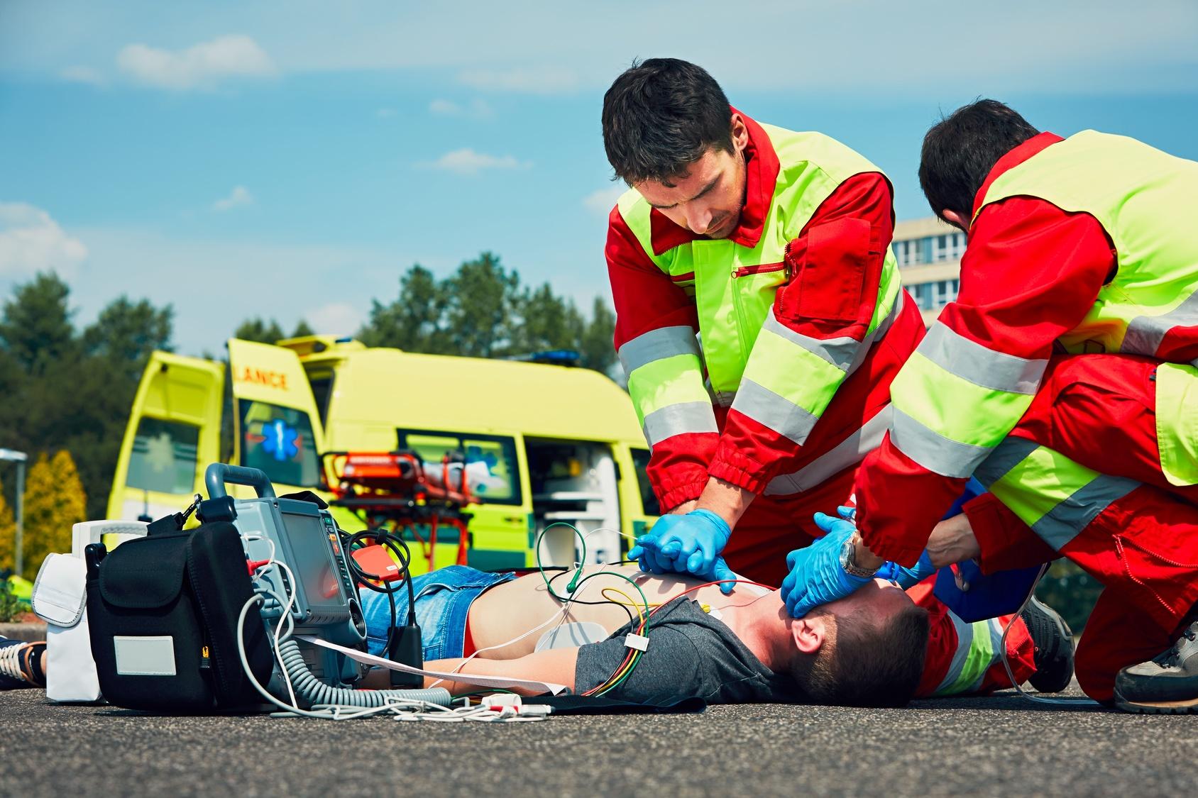 Zwei Rettungssanitäter reanimieren eine am Boden liegende Person
