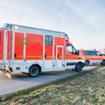 zwei Rettungswagen und ein Notarztwagen stehen einsatzbereit am Straßenrand. /Rettungssanitäter)