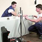 Zwei SHK-Handwerker installieren eine Badewanne