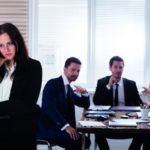 Mobbing am Arbeitsplatz: Drei Mitarbeiter reden hinter dem Rücken einer einzelnen Kollegin und zeigen mit dem Finger auf diese. Die Betroffene sieht nachdenklich sowie traurig in die entgegengesetzte Richtung.