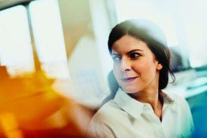 Mobbing am Arbeitsplatz: Eine Mitarbeiterin sieht nachdenklich durch den Raum.