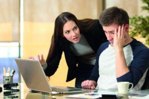 Mobbing am Arbeitsplatz: Ein Mitarbeiter guckt verzweifelt auf seinen Laptop. Die Vorgesetzte zeigt auf diesen und verzieht dabei das Gesicht.