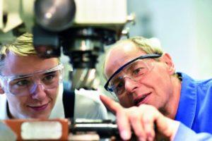 Ein Präzisionswerkzeugmechaniker zeigt einem Auszubildenden die Arbeit an den Maschinen.