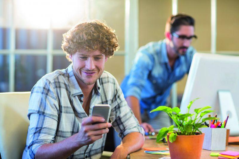 Ein Arbeitnehmer schaut glücklich auf sein Smartphone, während neben ihm gearbeitet wird.