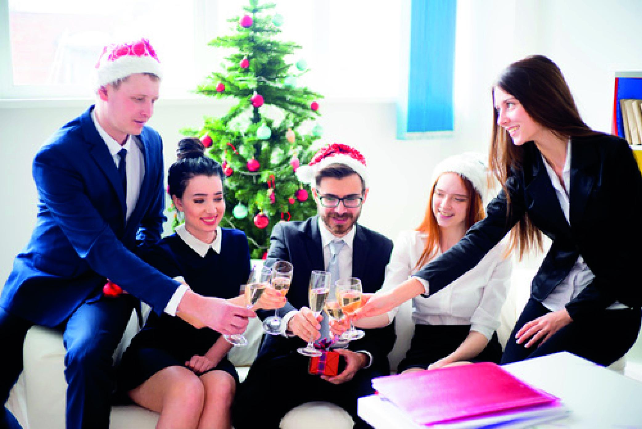 Neben dem Weihnachtsgeld auch die Weihnachtsfeier: Eine Gruppe von Arbeitnehmern stoßen gemeinsam auf eine gute Zusammenarbeit an.