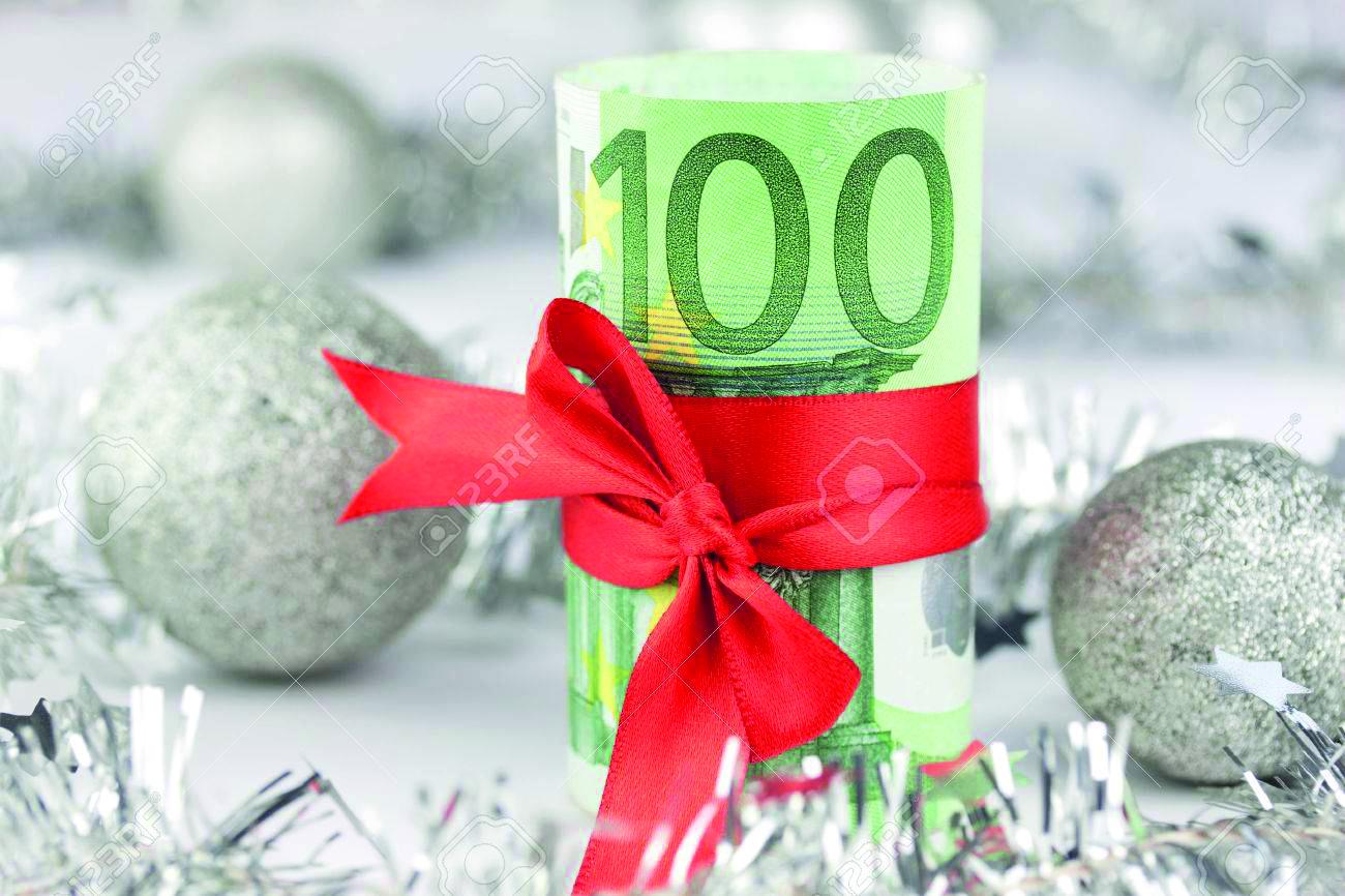 Weihnachtsgeld: Eine Rolle Geldscheine umwickelt mit einer roten Schleife.