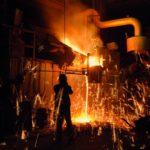 Verfahrenstechnologen Metall: Ein Facharbeiter stellt Metall her, um ihn herum sprühen Funken.