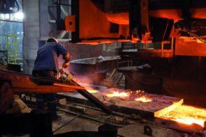 Verfahrenstechnologen Metall: Ein Facharbeiter formt Metall um. An seiner Arbeitsfläche ist offenes Feuer vorhanden.