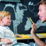 Ein kleiner Junge und ein erwachsender Mann sitzen sich gegenüber, schauen sich an und strecken jeweils die Zunge zur Nasenspitze. (Logopädie)