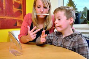 """Ein kleiner Junge und eine erwachsende Frau sitzen nebeneinander, haben beide einen Holzstab zwischen den Lippen und zeigen mit den Fingern die Zahl """"drei"""". (Logopädie)"""