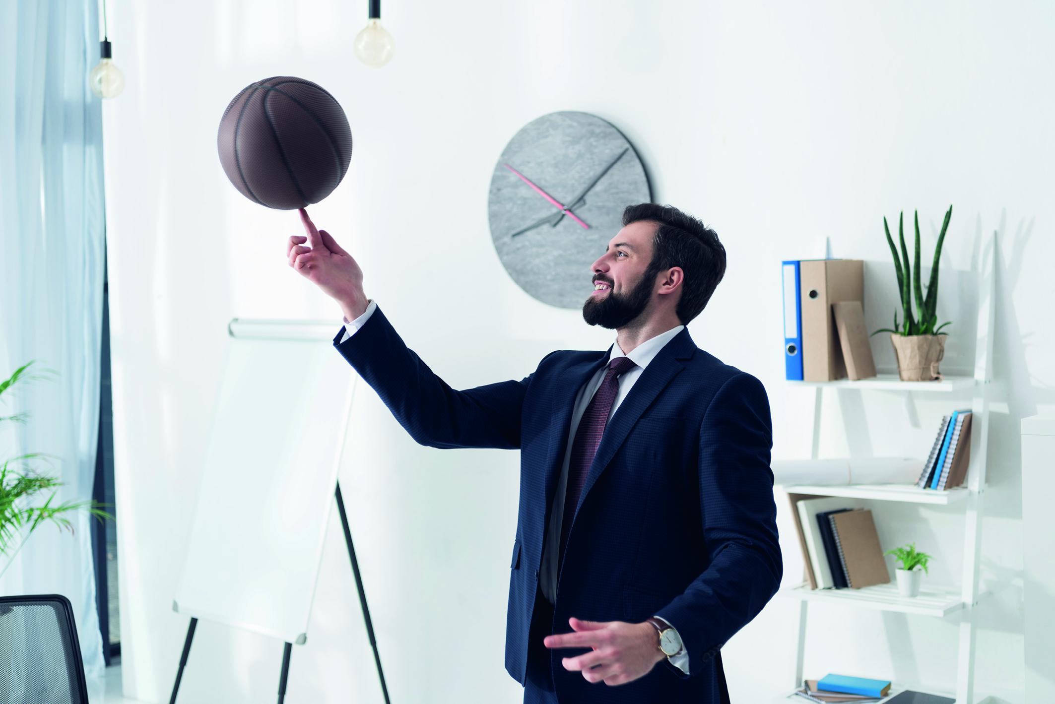 Ein Mann im Anzug spielt mit einem Basketball im Büro und lächelt. (Brückenteilzeit)