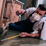 Ein Facharbeiter liegt auf dem Boden, trägt einen Mundschutz und bearbeitet den Boden. (Gebäudereiniger)