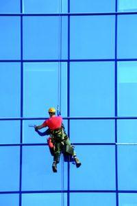 Ein Facharbeiter hängt an einem Seil in der Luft und reinigt eine große Fensterfront. (Gebäudereiniger)