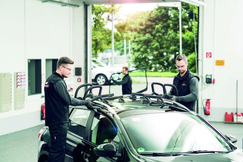 Autoglas-Spezialisten: zwei Männer halten ein Gerät an die Autogläser