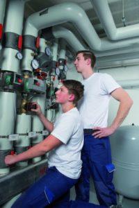 Zwei junge Facharbeiter prüfen eine Anlage. (Metallverarbeitung)