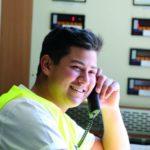 Ein Verfahrensmechaniker in gelber Warnweste telefoniert und lächelt dabei.