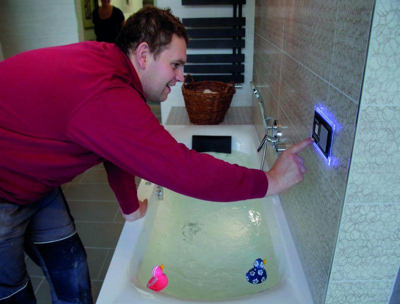 Ein Facharbeiter lässt Wasser in eine Badewanne laufen und steuert dies durch ein Touchpad an der Wand.