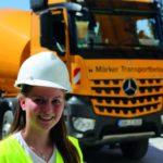 Eine Frau trägt einen Schutzhelm und steht vor einem Lastwagen Betonmischer (Frauen im Baugewerbe)