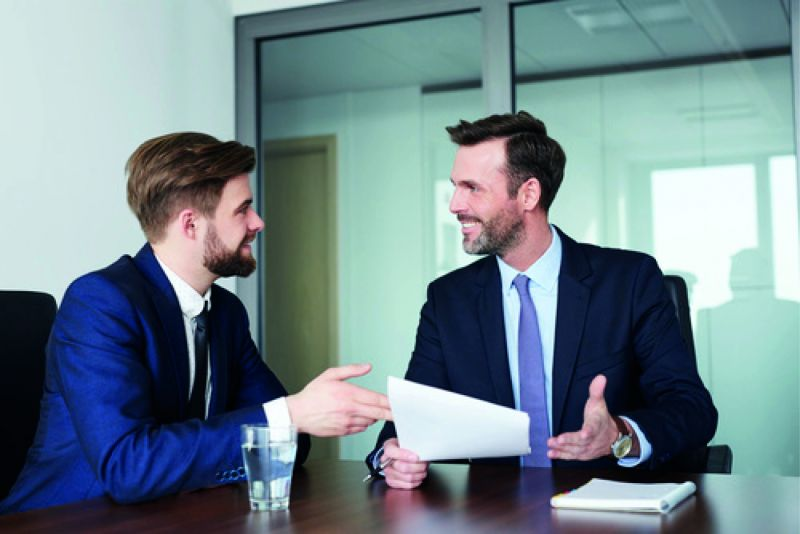 Zwei Männer in Anzügen unterhalten sich (Schweigepflicht im Job).