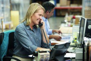 Eine Frau telefoniert und schaut dabei auf den Monitor ihres Computers (Logistik).