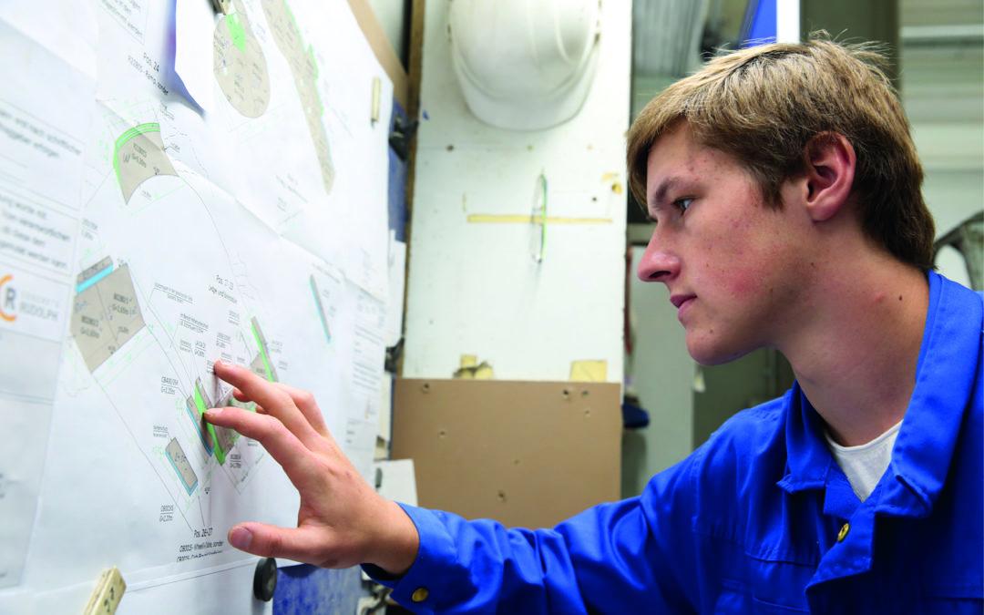 Ein junger Mann schaut sich Zeichnungen an (Betonfertigteilbauer).
