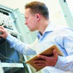Ein Fachinformatiker überprüft die Sicherungen eines Schaltschranks.