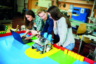 Drei junge Menschen stehen vor einem Roboter und bedienen einen Laptop (Digitalisierung).