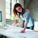 Eine Frau steht vor einem Schreibtisch. Schaut sich die Zeichnungen auf diesem an (Nebenjob).