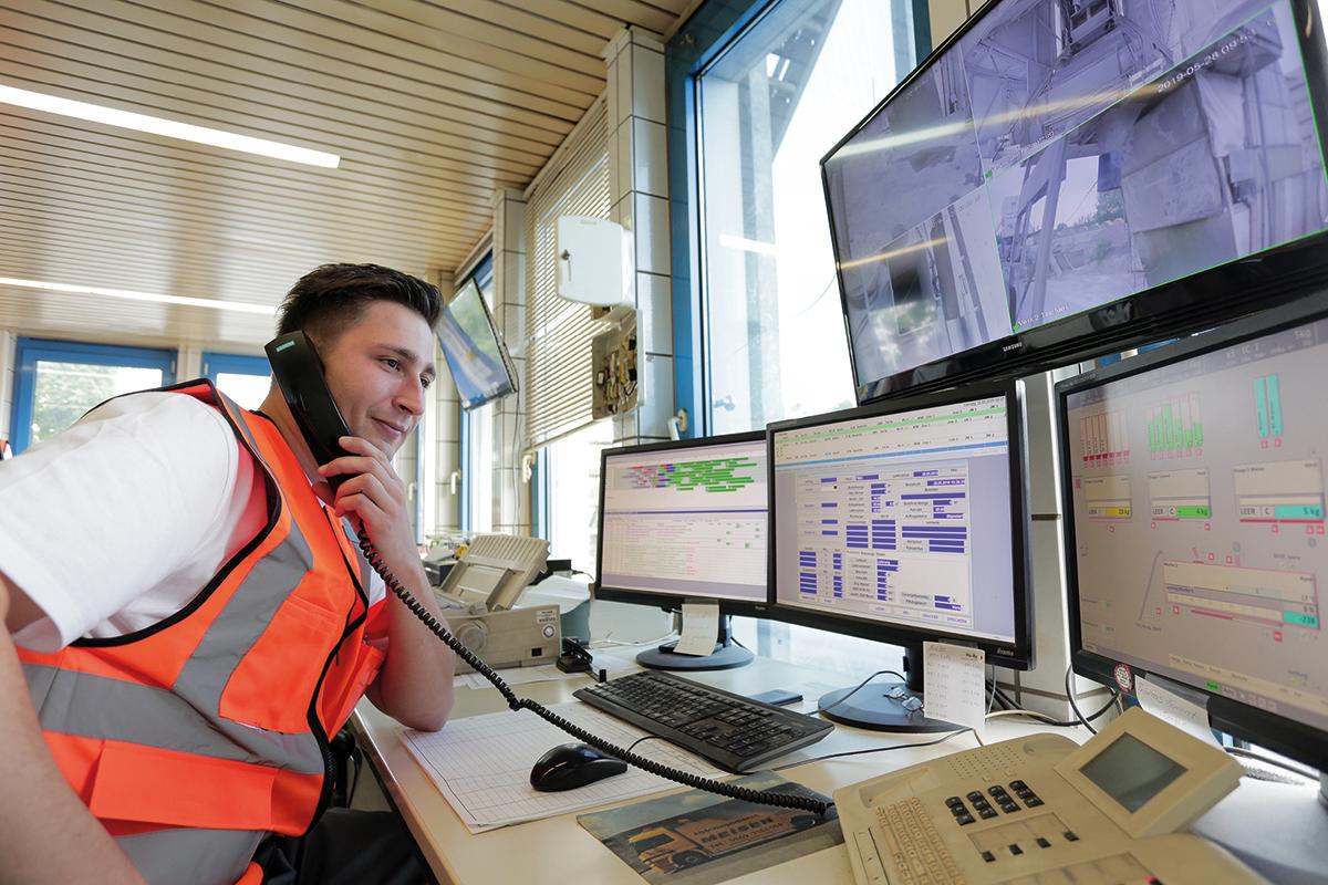 Eine Fachkraft sitzt vor drei Monitoren und telefoniert (Betonwerk).