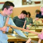Zwei Facharbeiter arbeiten gemeinsam an einer Säge (Berufsstart)
