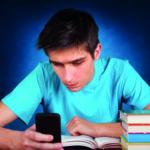 Ein Junge sitzt an einem Tisch, auf dem Bücher gestapelt sind und bedient sein Smartphone (Digitale Medien).